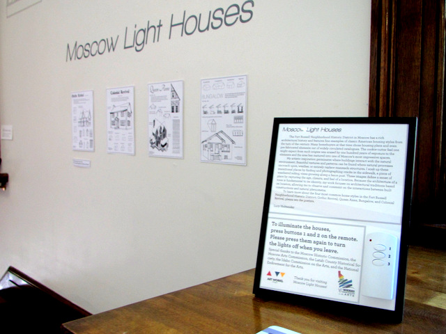 Artist statement with directions for lighting. Posters describing common architectural styles in Moscow's Fort Russell Historic District hang on the wall behind.