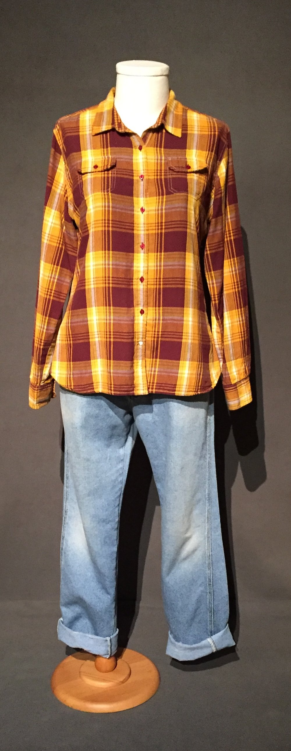 "- Flannel shirt, denim pants; Owner – Lyadonna, bi-sexual, woman, 32, lives in Iowa; c. 2010s""If I'm going to be around this group of women, what are their expectations going to be, and what should I wear and I. I had this one, camping shirt or you know it's from an Outback store and, it's plaid and it's also kind of Iowa State colors and I was like, I'm definitely wearing that for this trip, so, I will fit right in. I got there, and I didn't at all. It was funny. I looked like a lumberjack, but, everyone else was wearing these, just these t-shirts that had these big rainbows on them, so, you know, it was funny, but I have thought about this before, you know, oh I'm going out in this, is this"
