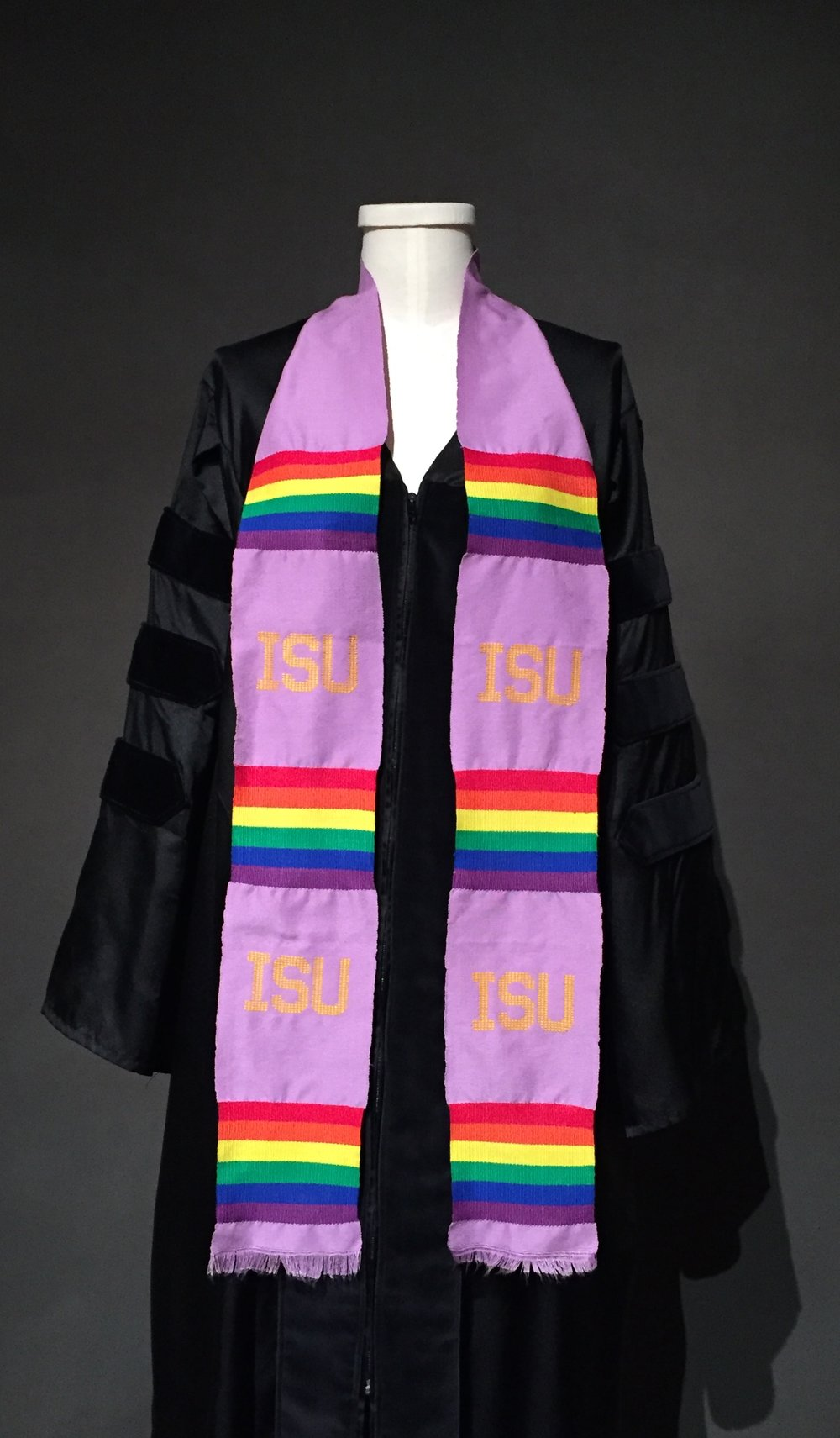 "- Graduation robe, lavender graduation stole with ISU motif; Owner – LGBTQIA+ Student Success Center at Iowa State University; c. 2010sGraduation robe, Iowa State University's Textiles and Clothing Museum""The inverted pink triangle motif was the original stole, but we moved away from it because it resonated with students less and then also just more of an emphasis on participation of ISU."" –personal interview with Clare Lemke, Assistant Director of the LGBTQIA+ Student Success Center at Iowa State University, September, 2017"