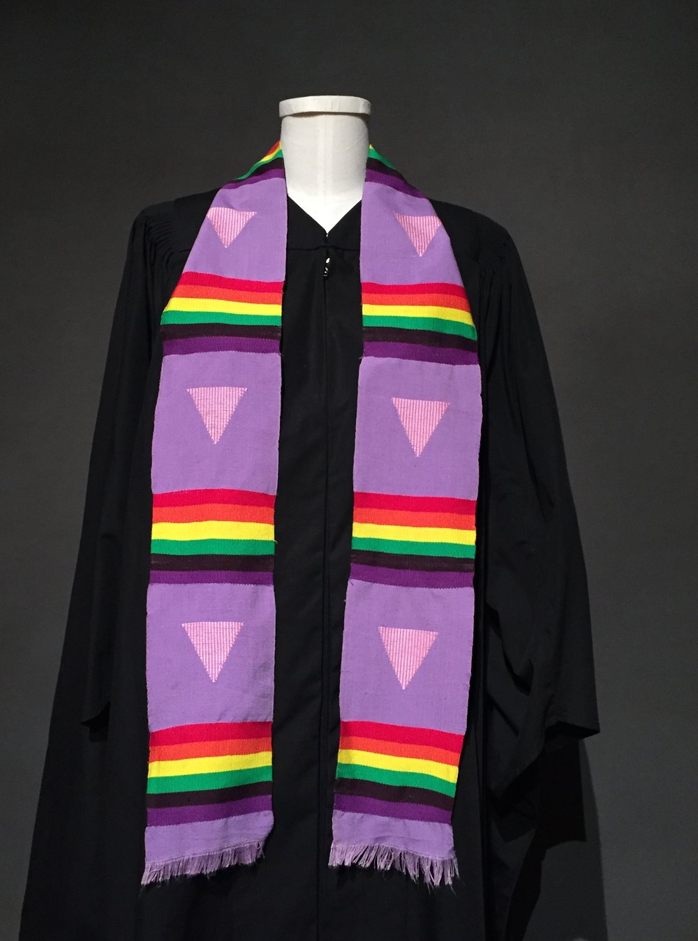 "- Graduation robe, lavender graduation stole with triangle motif; Owner – LGBTQIA+ Student Success Center at Iowa State University; c. 1990sGraduation robe, Fashion & Culture Research Lab at Iowa State University""Lavender Graduation started around 1997 or 1998. The first 15 years of the program [the Lavender Graduation] we gave rainbow tassels that you would add, but you could not wear it at graduation. They didn't allow you to at the official graduation ceremony because each college has its own tassel. I don't remember what year it was, but what we realized was we could start wearing stoles. The stoles could be added and worn, and we got permission to do that and so we started giving the graduates stoles. The first year at Lavender Graduation, we had a 6 to 8 [students] participate where as now we have about 25-30 participate, and they get a stole that they get to wear at the graduation ceremony."" –personal interview with Brad Freihoefer, Director of the LGBTQIA+ Student Success Center at Iowa State University, September, 2017"