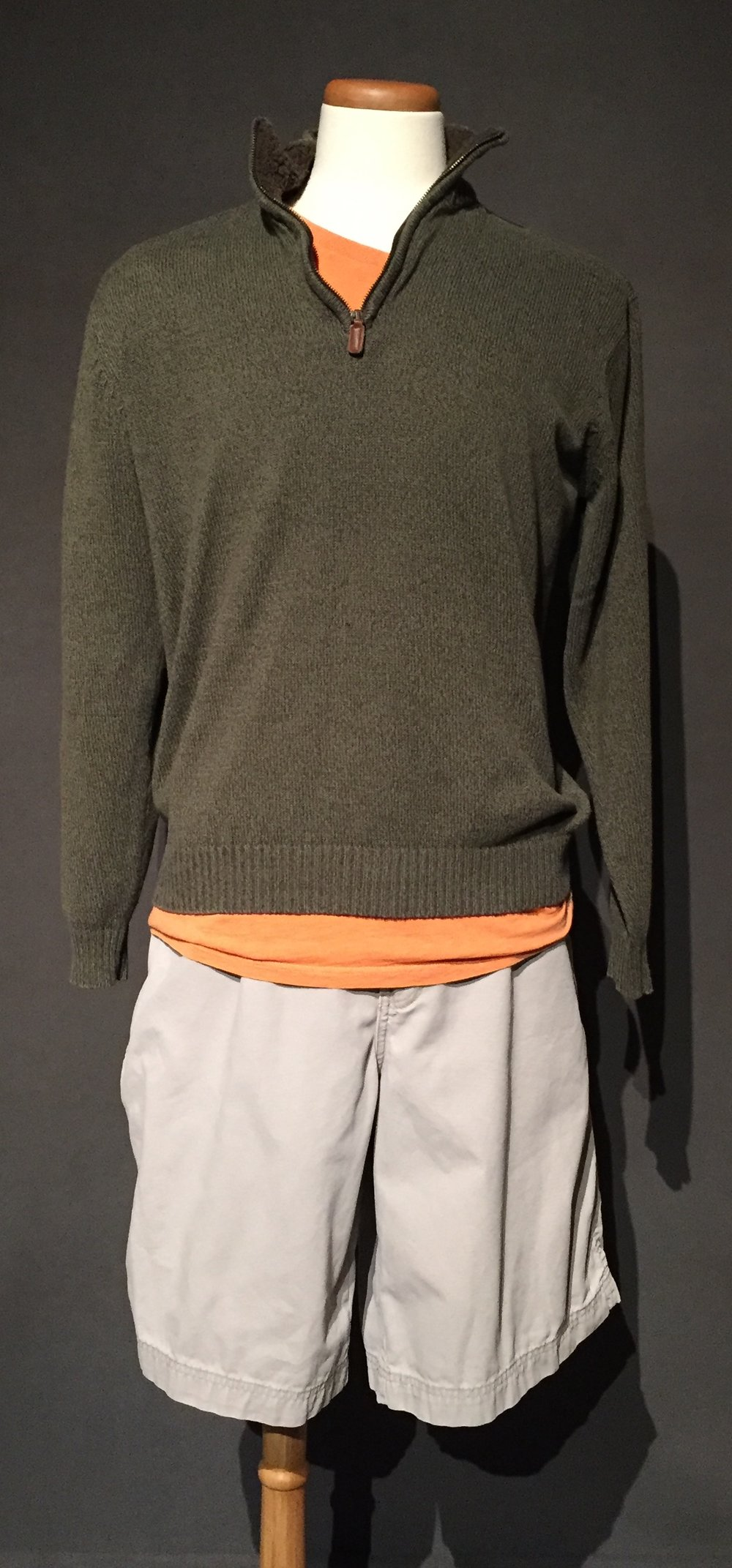 """- Green sweater, orange t-shirt, tan cargo shortsOwner – Kai, gay, woman, 43, lives in Iowac. 2010s""""I prefer men's [clothes] you know, I'm attracted to most things that are men's styles.""""""""Anything cargo I'm all in, I just think they're great, how could you ever have too many pockets?""""""""Because its an automatic assumption [that she's gay], and because I look the way that I do [masculine] I don't always get to make that choice [to disclose her sexuality or not], and there are days when I don't want to carry the sword. There are days where, I don't want to have to say I'm gay or I'm married to a woman, or there's days where I'm just tired and I just want to be able to easily move through this interaction and move on and I can't because of the way I look. That's probably one of the more difficult aspects I think. I'm coming out all of the time because of the way I look whether I want to or not."""" -personal interview with Kai, October 17th, 2017"""