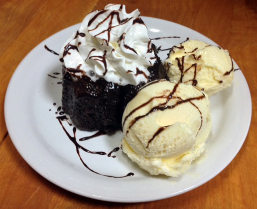 Chocolate Gnash Lava Cake With Vanilla Ice Cream toped with Whipped Cream and Chocolate Drizzle