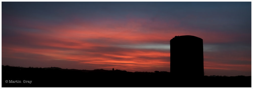 'Before the Sun'... L'Ancresse Common with a Martello Tower and red sky...