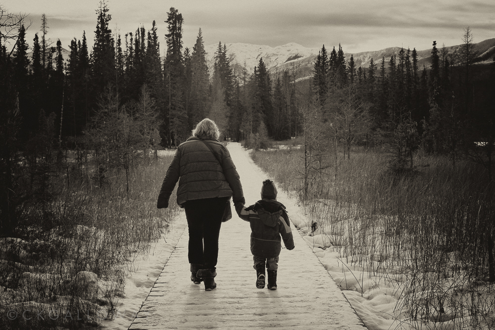Gran and grandson, hand in hand on the trail at Liard Hot Springs, November 2014.