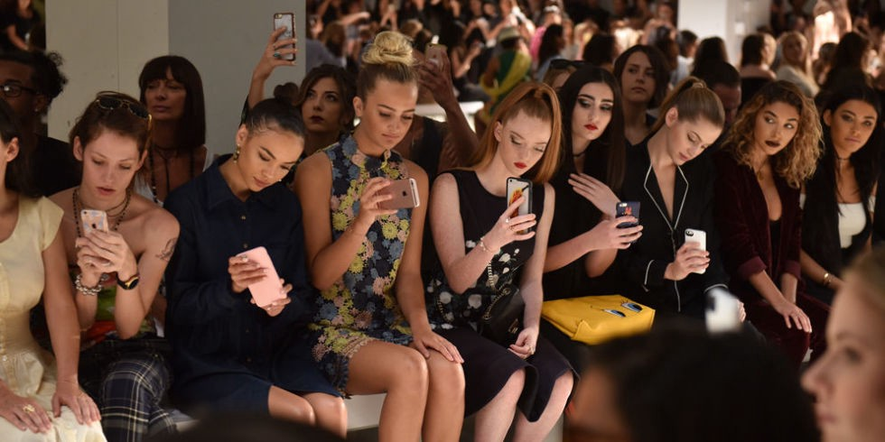 Cell phones out at a fashion show.