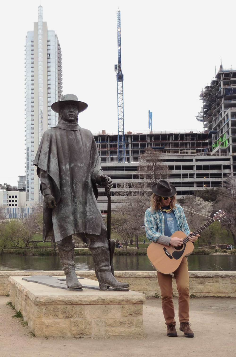 Matty busking by Stevie Ray's statue