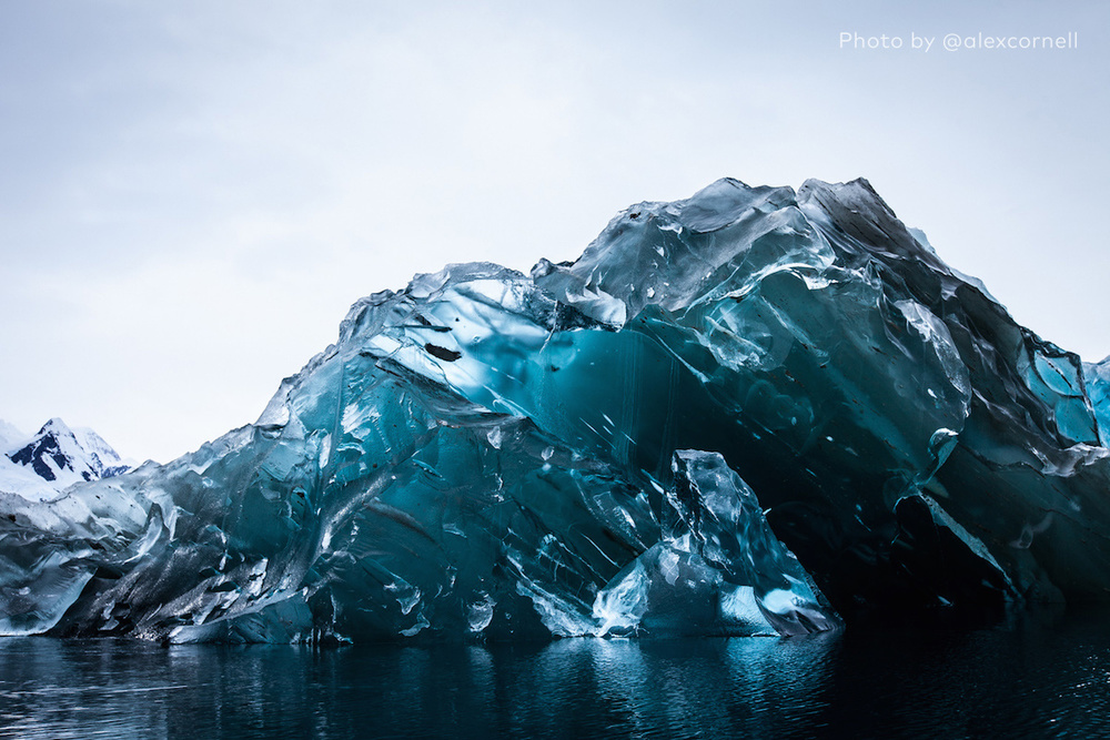 A glassy blue iceberg, free of snow.