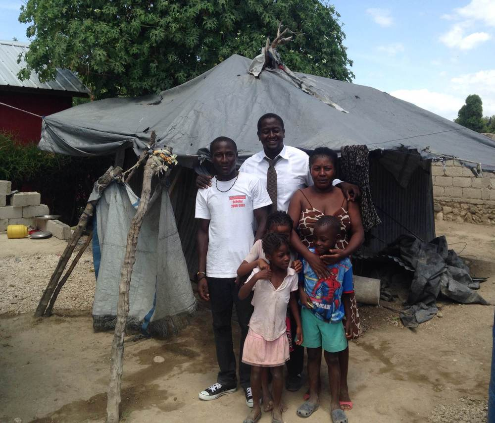 Maculla, her younger children, and her eldest son stand in front of their previous shelter with our In-Country Director, Jimmy.