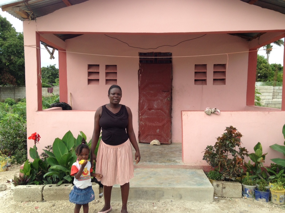 Simone, a resident of Croix-des-Bouquets, stands in front of her new home.