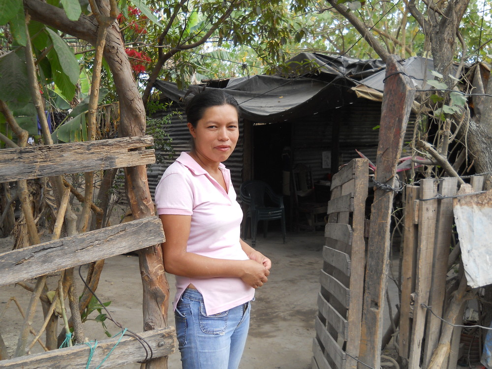 A woman in The Romero Community stands in front of the shack where she lives.
