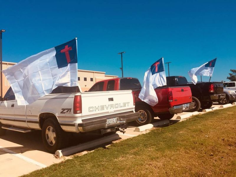 students displaying Christian flag on their cars