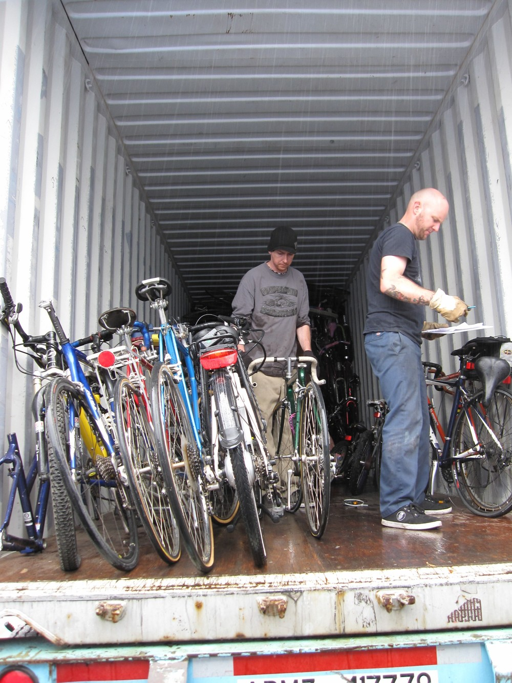 Nick (the guy in the black hat) is loading one of the carbon fiber bikes that got donated this bike drive. These bikes are going to the MK Cycles racing team.