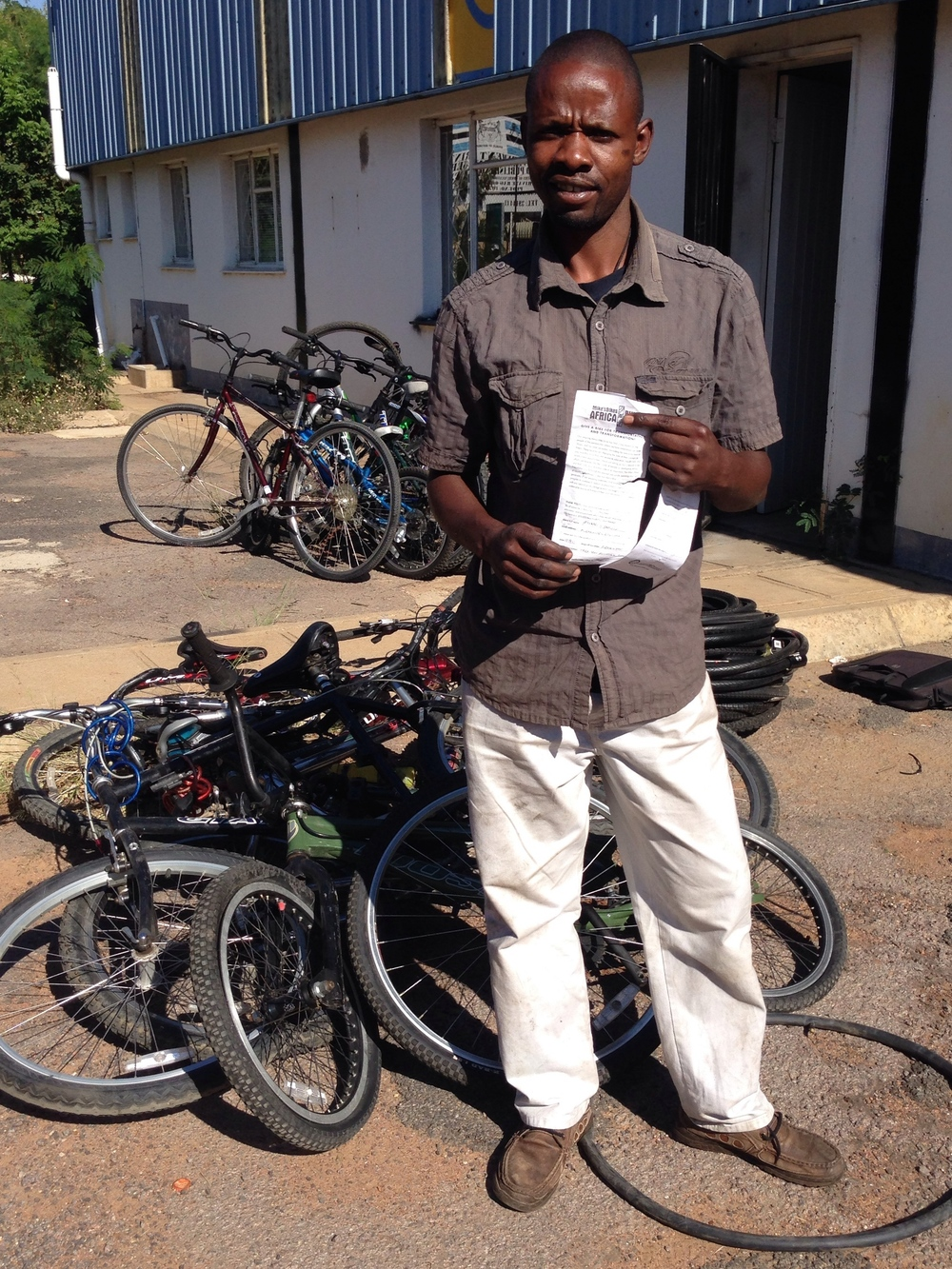 Enoch with his new stock and slips from our bike donors in California.
