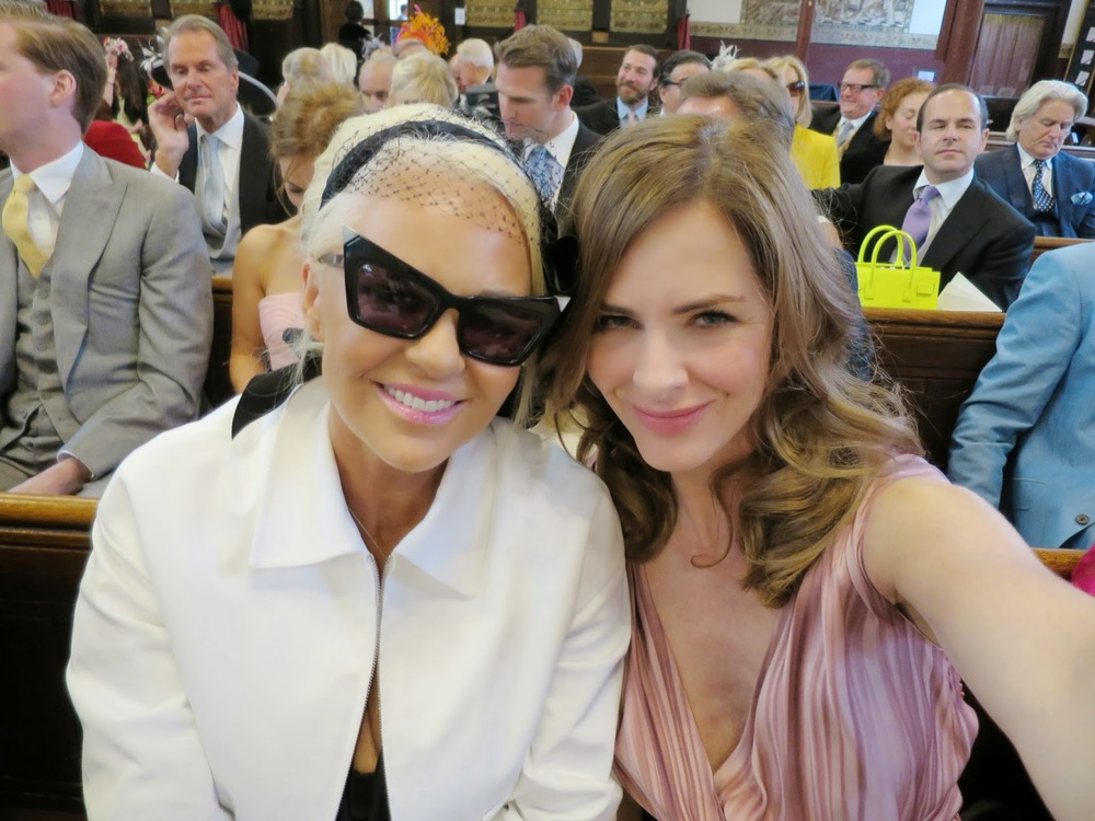 Amanda Eliasch with Stephen Jones hat and Andy Wang glasses, white Prada jacket with Trinny Woodall in Vintage Prada.
