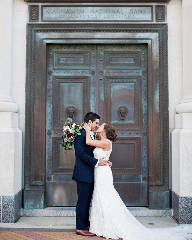 "Mr. & Mrs. Biondini moments after saying ""I do"" outside the beautiful Calcasieu Marine Bank!⠀⠀ ⠀⠀ #emilyanddaniel #weddingphotography #weddingphotographer #lakecharles #louisianawedding #outdoorwedding #laceweddingdress #downtownwedding"