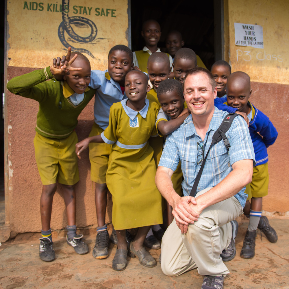 Henry Vanderspek pictured with children from the Raising Voices project in Uganda.