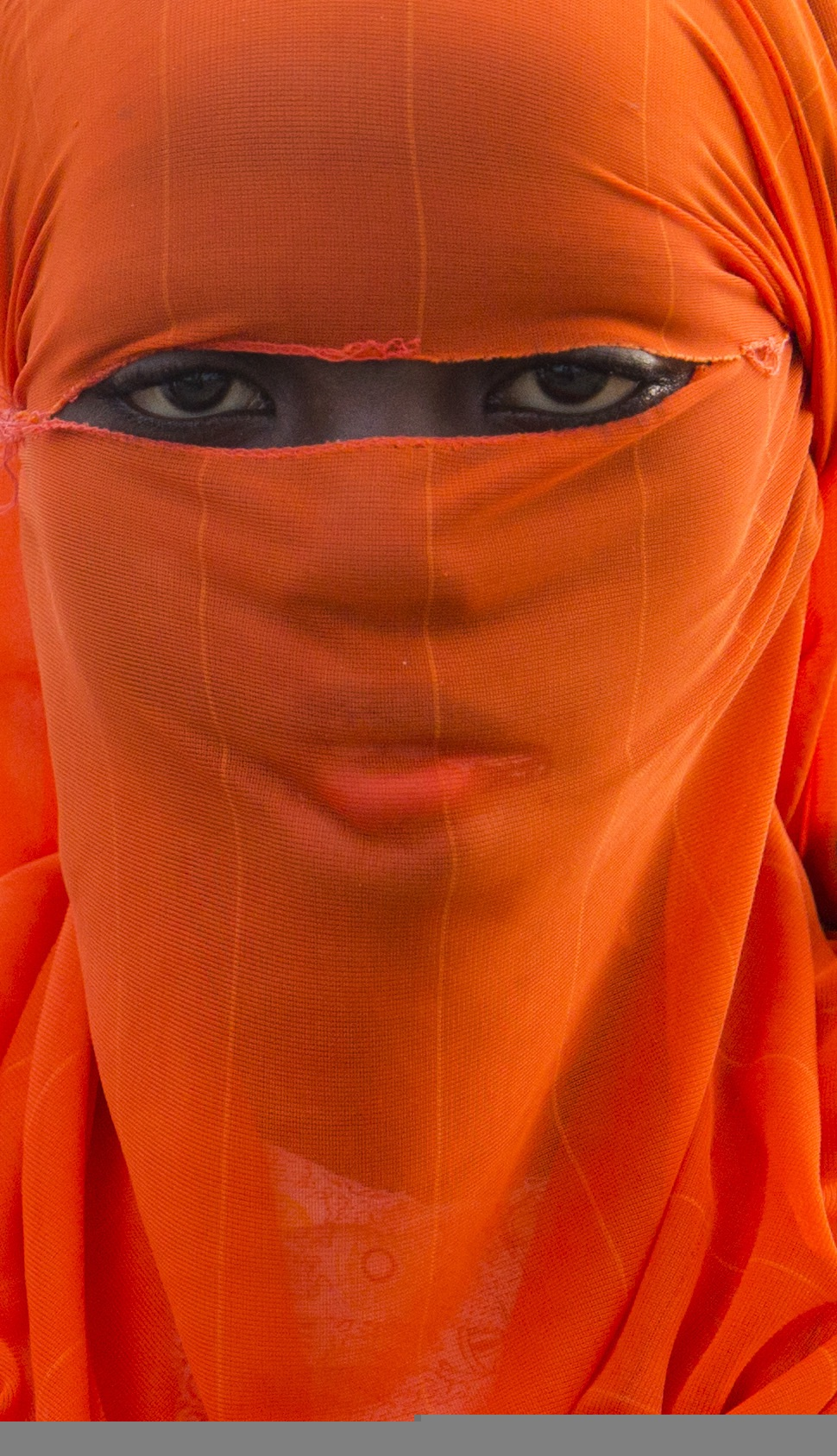 A young girl covers her face, traditional of the Muslim culture of Zanzibar, Africa.Photo by Kelly Wenzel