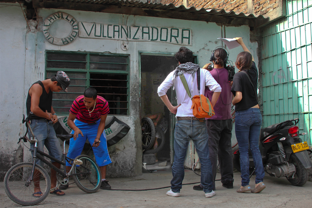 DIRECTOR CLAUDIA QUIGUA, ASSISTING CAMERA OPERATORS WHILE SHOOTING THE ZORRERO ( CART DRIVER) AT THE TIRE REPAIR SHOP IN CALI, COLOMBIA. //PHOTOGRAPHY BY NELSON GOMEZ FOR THE GLOBAL LIVES PROJECT