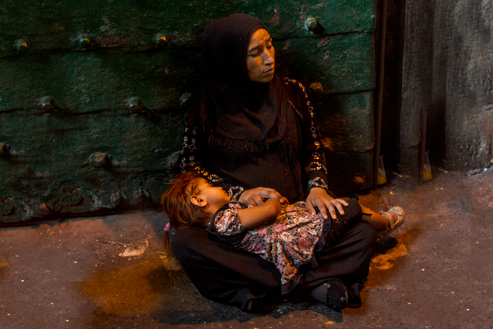 A woman holds her toddler while begging for money at the Grand Bazaar in Istanbul, Turkey which attracts between 250,000 and 400,000 visitors daily.//Photography by Claudia Quigua