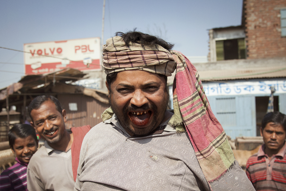 A worker in the boat yard in Old Dhaka showing off his betel nut dyed tongue. similar to chewing tabacco, the betel nut is a common social practice in dhaka. // photo by tobi ann.