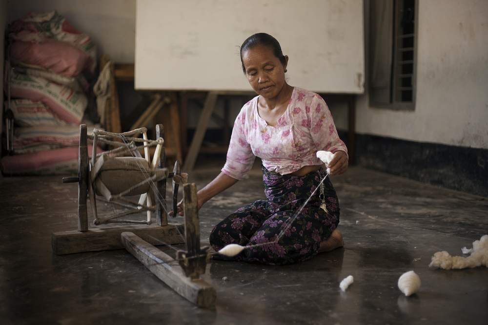 A woman from the Tanchangya tribe in the Chittagong Hill Tracts in Bangladesh spins cotton that will later be used by the Tripura for weavings. //PHOTO By TOBI ANN.