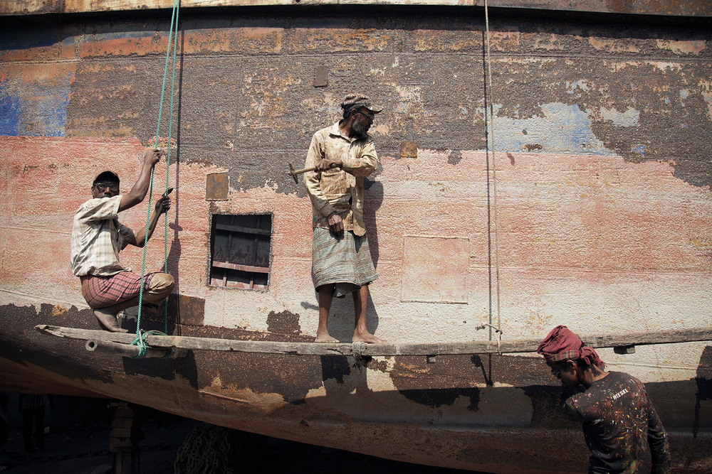 Three men working in the boat yard in Old Dhaka. They spend the day hammering the sides of the ship looking for soft rusted metal.//PHOTO BY: TOBI ANN