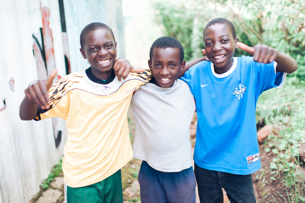castori (right) poses with two of his friends.Now that he is has been living in the children's village for some time, castori has blossomed into a charismatic confident young man with ambition and joy for life.Photo by Aimi Duong.