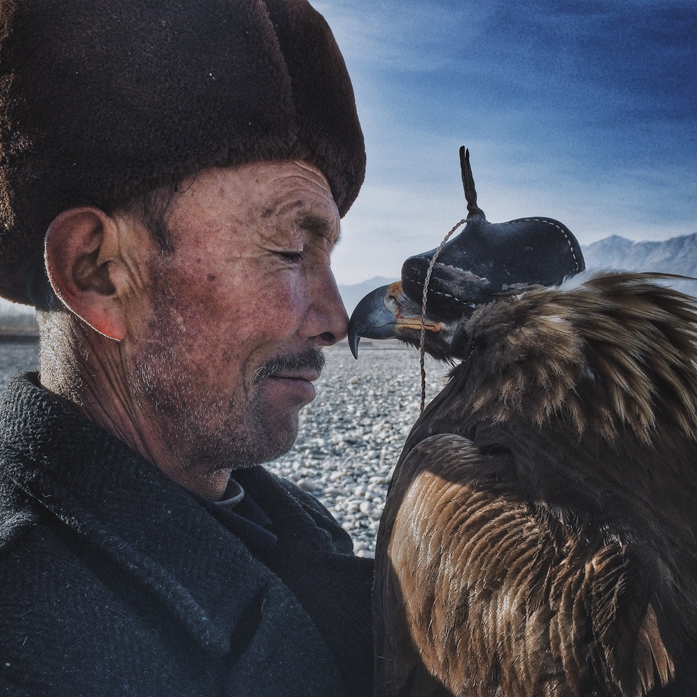 """Siyuan Niu Xinjiang, China Grand Prize Winner,Photographer of the Year Man and the Eagle """"The brave and wise Khalkhas live along the mountains in the south of Xinjiang and are companions with the eagles. They regard eagles as their children and train them for many years to hunt. This 70 year old man is rigid and solemn in front of family and friends, but when he is with his beloved eagle, the corner of his mouth would curve up. When the eagles reach mating age, although he is very reluctant, the man releases the eagles back into nature so that they can thrive. A mild heart and exquisite love are covered by his weather-beaten face. He is a tough man with a tender heart."""""""