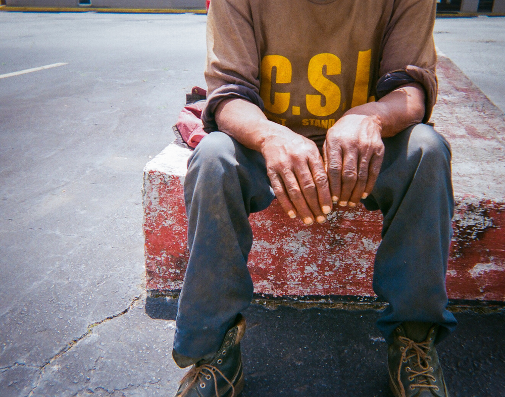"""Hangin' Outby Ray Kelly """"This man is homeless. He didn't want his face in the picture. He was just hangin' out because that's what homeless people do. They hang out and wait for food or for a place to open. They wait for something to happen."""""""