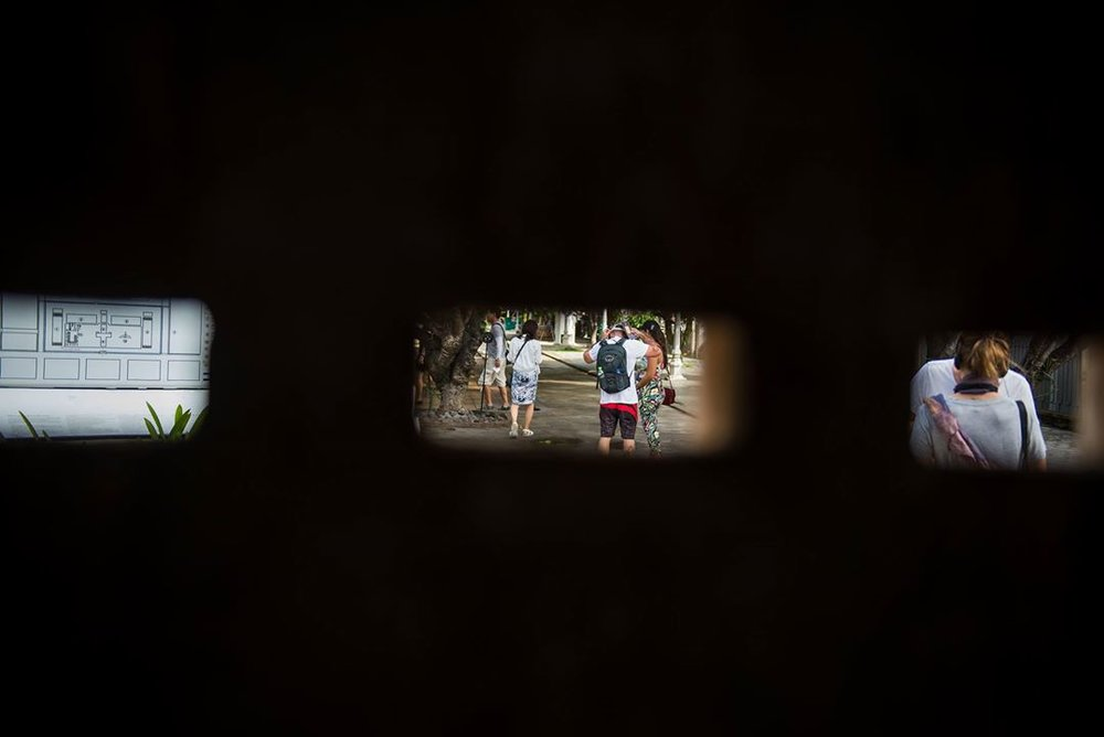 Past and present: looking outside from within the Khmer Prison watching visitors to Cambodia take in its history. PHOTO: Anita Bonnarens