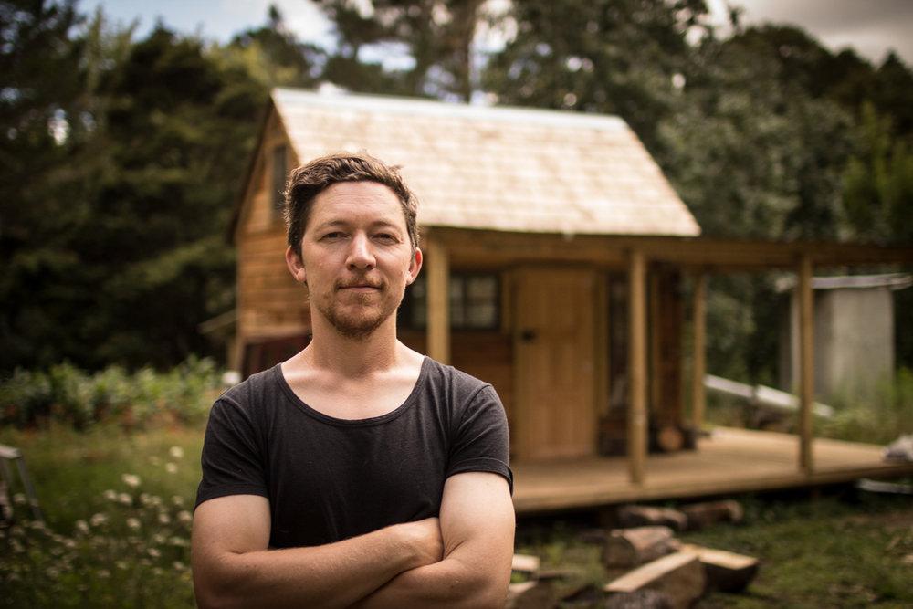 Toby outside his custom built cedar wood cabin home studio, in northland, New Zealand.