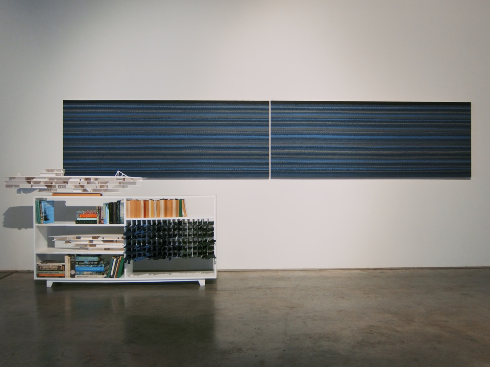 Built plywood cabinet containing books (adventure novels, woodworking manuals, scuba diving field guides, and sailing handbooks), cut paper waves, and foam ship models, sitting underneath a depiction of the sea from cut paper waves glued to plywood panel, 16x2x6 feet, 2014.