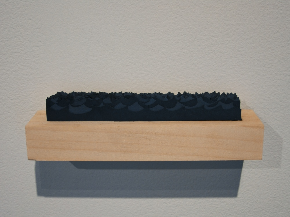 Carved wooden box containing stacked cut paper waves, 6x1x1 inch, 2014.