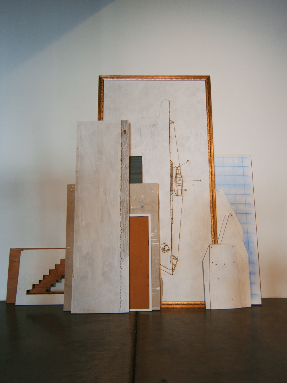 Various plywood scraps leaning against the wall containing abandoned projects that have been wood-burned, painted, and cut into, 8x8 feet, 2014.