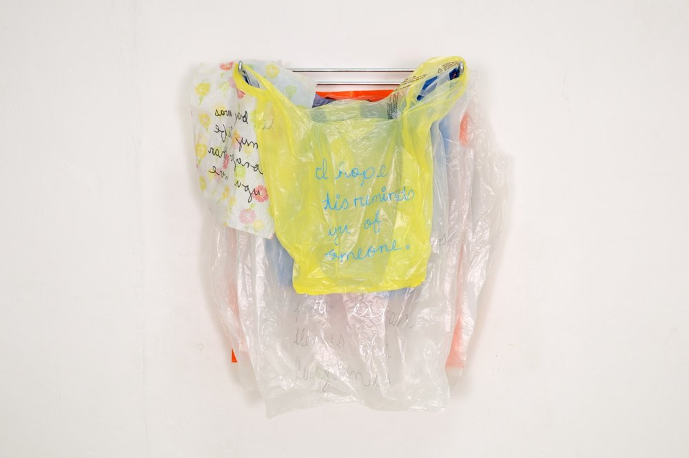Made at University of Texas at El Paso in bricolage(assemblage)/mixed media, (detail) embroidered found plastic bags hanging on grocery store plastic bag dispensers, 10x2 feet, 2016.
