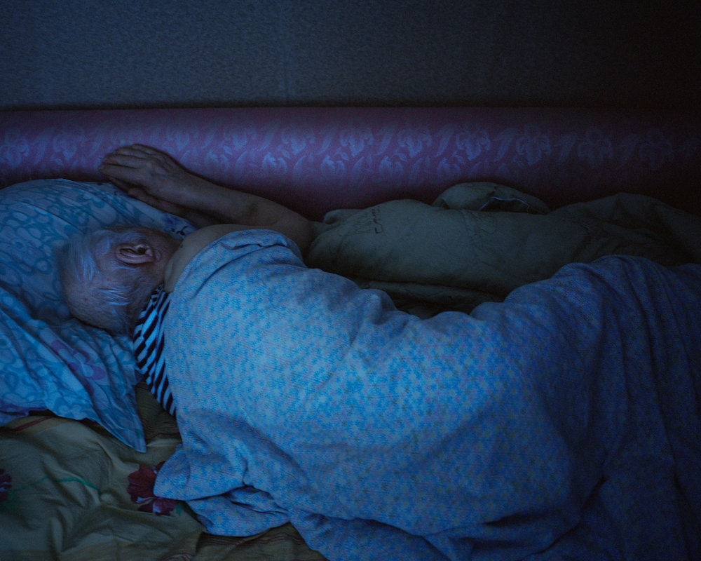 Smirnov asleep in his apartment in Zapolyarny, Russia. He moved to the town in 1970, when the drilling began.