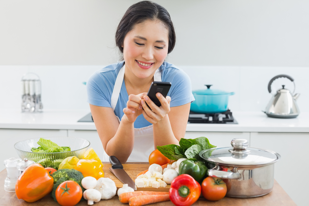 stock-photo-woman-using-mobile-phone-while-shopping-in-supermarket-vegetable-department-store-159877106.jpg