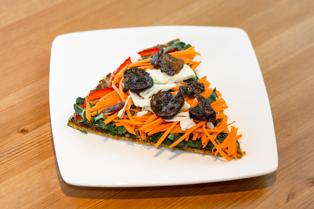 Rawkin' Pizza    Wheat free sprouted buckwheat crust, dill nut cheese, sweet chili sauce, chiffonade kale, julienne carrots, cauliflower, and marinated mushrooms.