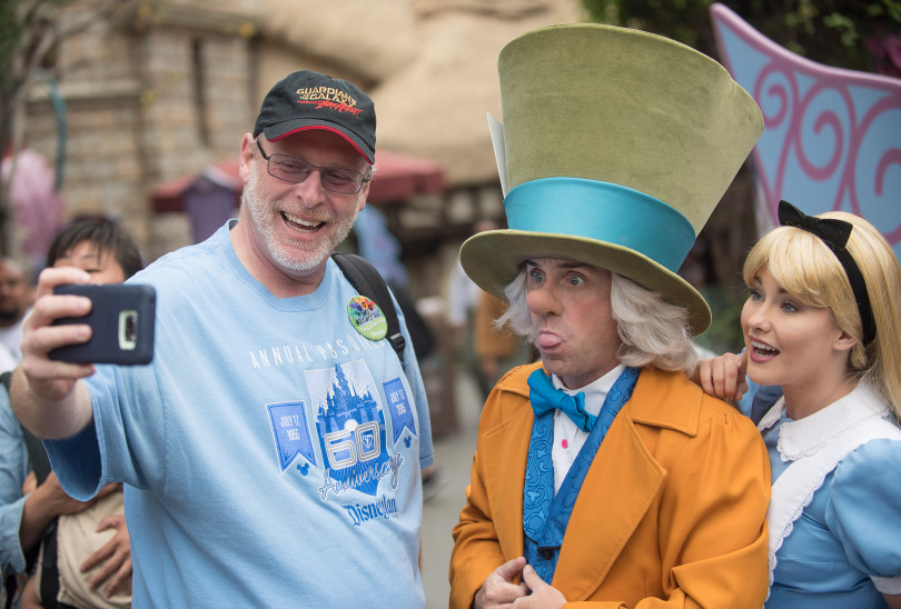 Jeff Reitz takes a selfie with the Mad Hatter and Alice after telling them of his feat of going to Disneyland for 2,000 days in a row in Anaheim, on Thursday, June 22, 2017. (Photo by Nick Agro, Orange County Register/SCNG)