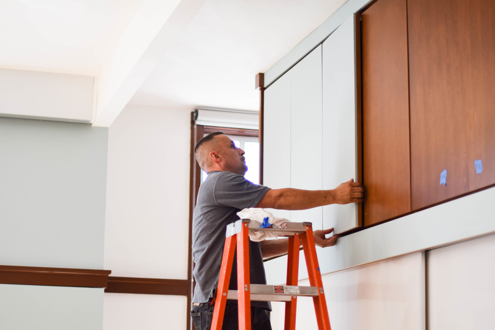 Manuel installing the acoustical tackable panels on the cabinet doors