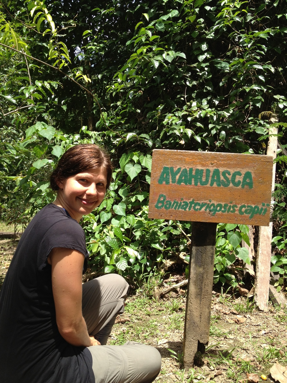 Rochelle next to the Ayahuasca vine in the Amazon jungle of Peru.