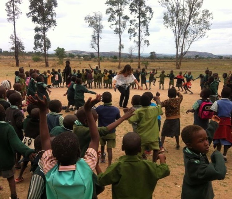 """One of my favorite moments on the Qoya Service & Safari retreats is working with local school children. This photo is of me leading 100+ children ages 4-7 through a Qoya class."" -Betsy Blankenbaker"