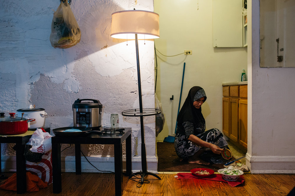 "Lalia Nobihousen prepares dinner for her family on the floor of their apartment in Roger's Park, Chicago. Laila and her husband share an apartment with another couple. The women first met during their escape from Myanmar by boat.""I can't forget my culture and my village and parents,"" Ms. Nobihousen said. ""We lived together. Everything, I can't forget. Right now I just think, one day we go back to our country and tell them we are American, educated people."""