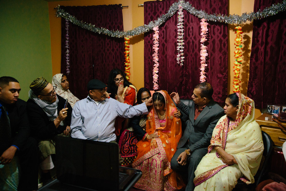 Razia, age 23 is surrounded by family members in Hamtramck, Michigan while they perform a marriage ceremony held over Skype to her husband in Syhlet, Bangladesh.