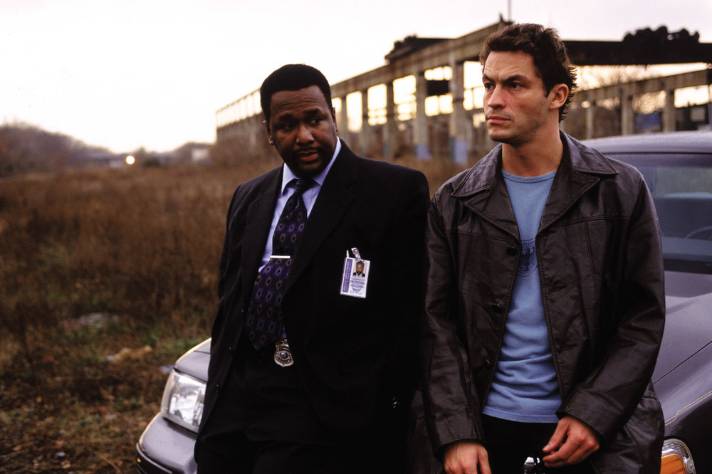 Dominic West as Detective Jimmy McNulty and Wendell Pierce as Detective William-The Wire.jpg