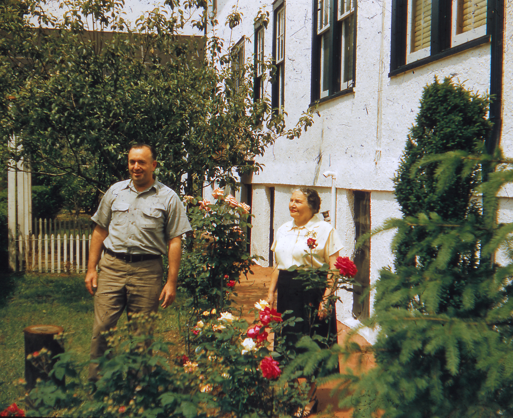 My Grandmother With My Uncle Davie Admiring Her Roses (Fruit Trees and Grape Vine In The Background)