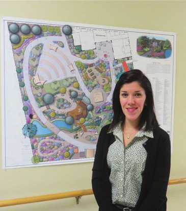 Iowa State University graduate student Alejandra Feliciano stands next to her team's proposal for the On With Life therapy garden.