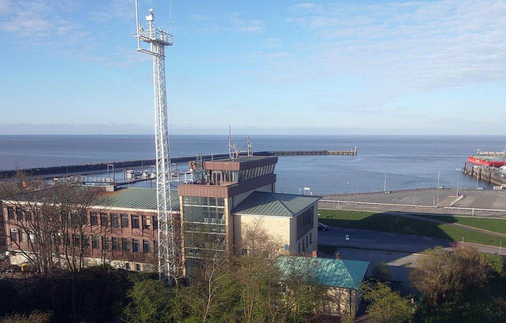 A view to the North Sea with the Staatliche Seefahrtschule Cuxhaven main building in the foreground.
