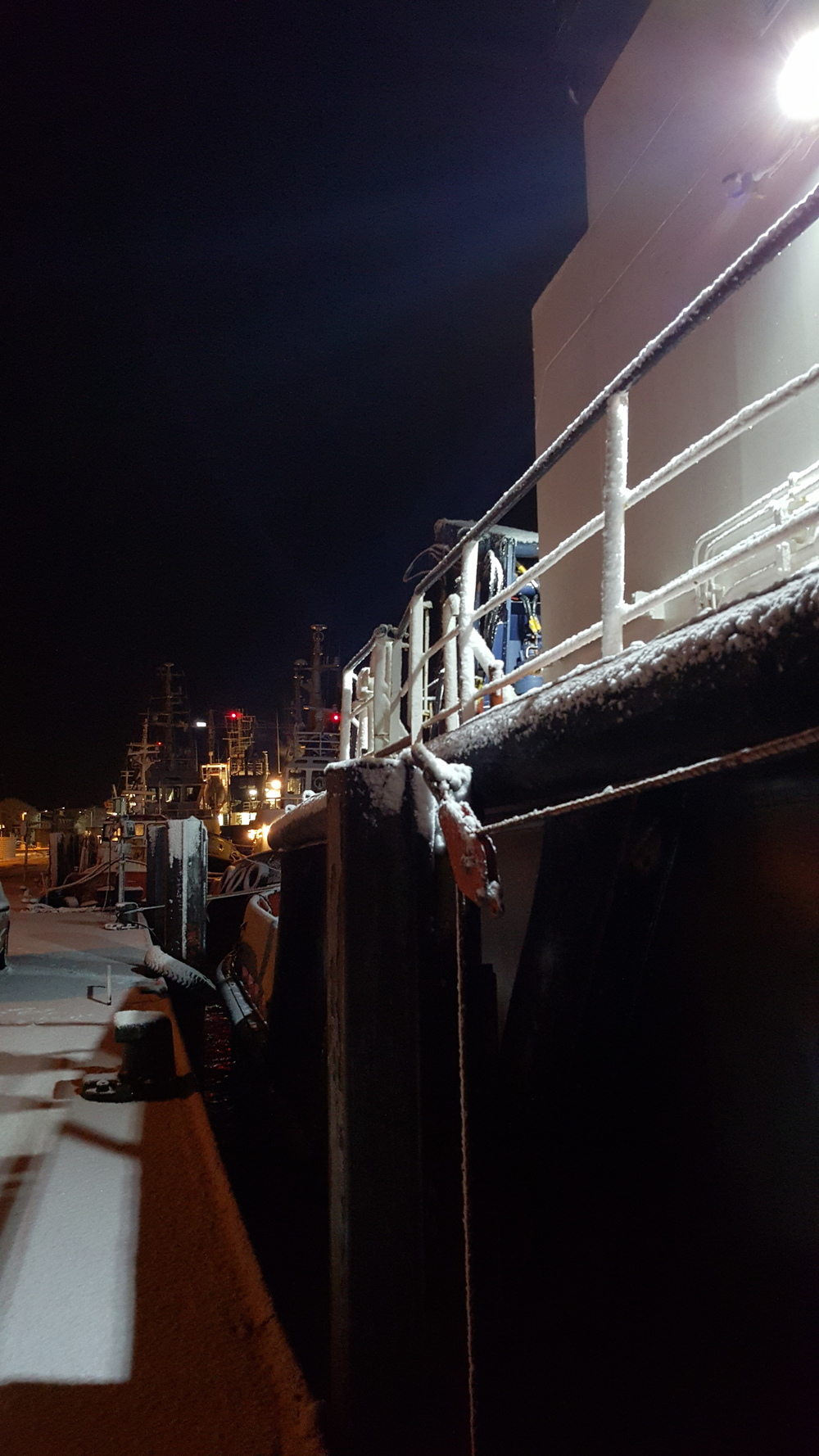 Otto Wulf tugboats in the port of Cuxhaven on an icy and wintry night.