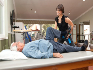 Rehabilitation staff member, bending patient's knee.